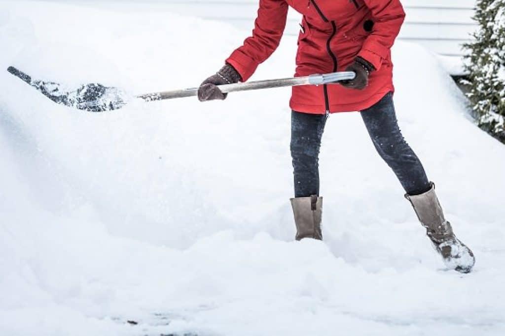 Donna con pala da neve